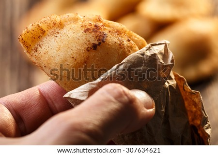 Male hand holding fried colombian empanada. Savory stuffed patties also known as pastel,pate or pirozhki - stock photo