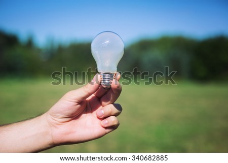 male hand holding light bulb. new idea concept - stock photo