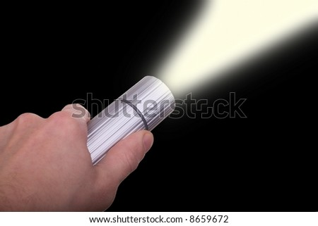 male hand holding lit flashlight in the night - stock photo