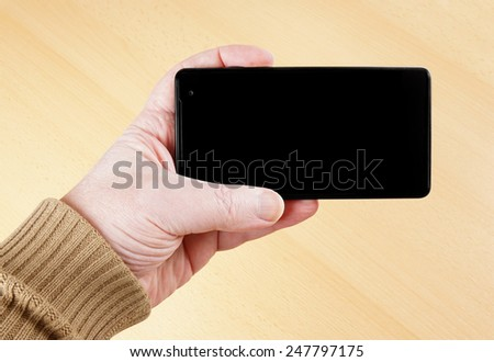 male hand holding mobile smart phone with blank display screen - stock photo