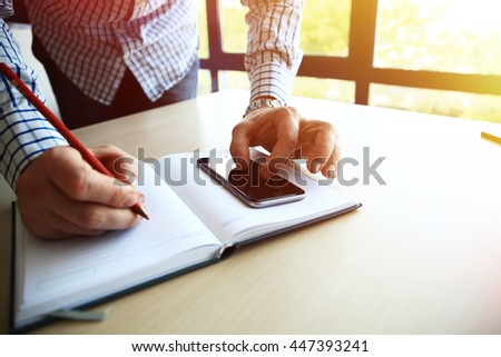 Male hand holding pencil ready to make note in opened notebook while looking at cellphone. Businessman or employee at workplace writing business ideas, plans or tasks at personal organizer
