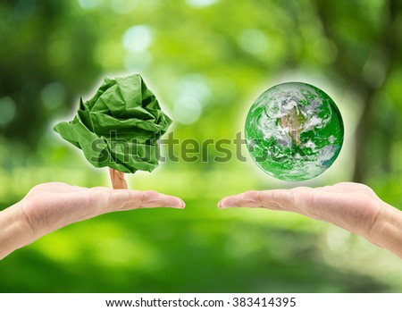 male hand holding planet and male hand holding paper shape tree on blurred green bokeh background of tree nature  : world environment day concept: Elements of this image furnished by NASA