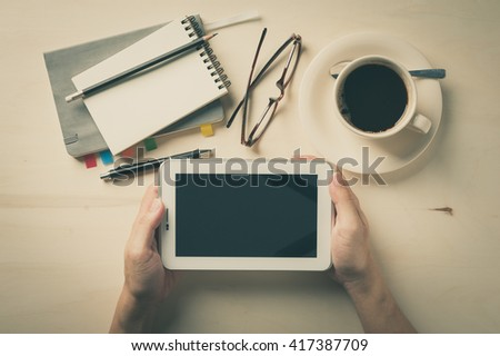 Male hand holding small tablet pc with notebooks, pen, and coffee cup beside on wood table in morning time with vintage filter effect