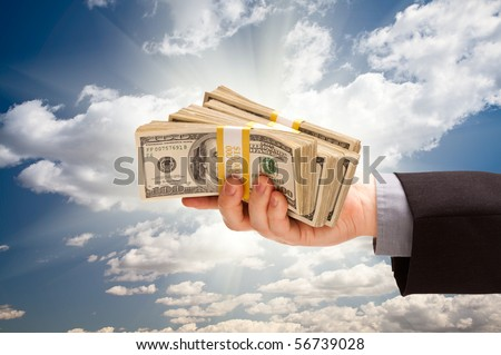 Male Hand Holding Stack of Cash Over Dramatic Clouds and Sky with Sun Rays. - stock photo