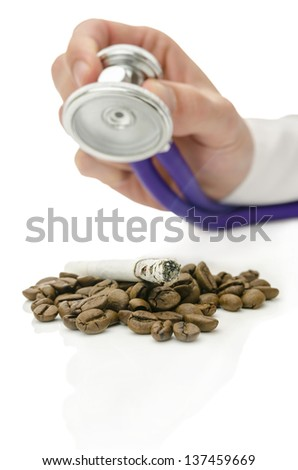 Male hand holding stethoscope over cigarette on coffee beans. Concept of help for smoking addiction. - stock photo