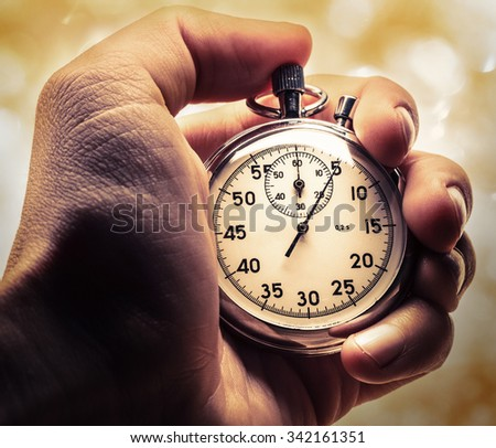Male hand holding stopwatch in dramatic light - stock photo