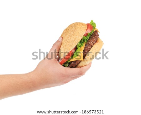 Male hand holding tasty hamburger. Isolated on a white background. - stock photo
