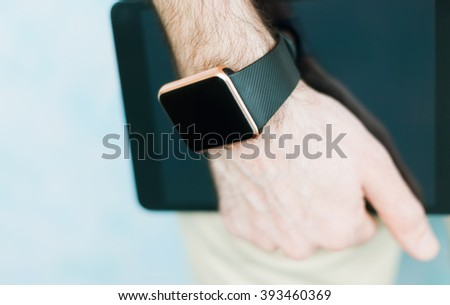 Male hand holding two modern digital devices to be always connected to internet and social media - trendy smart watch and tablet pc.  - stock photo
