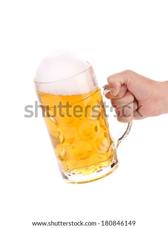 Male hand holding up a glass of beer. Isolated on a white background. - stock photo