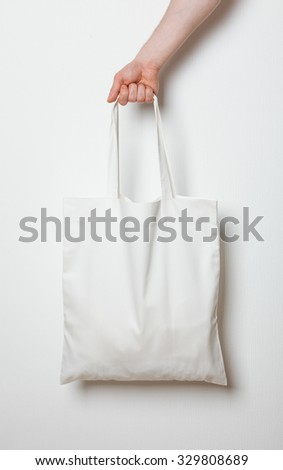 Male hand holding white textile bag, neutral background - stock photo
