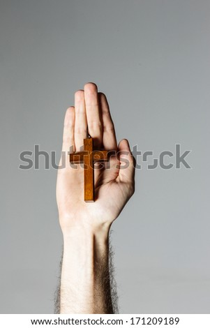 Male hand holding wooden cross on gray background - stock photo