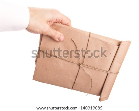 Male hand holds chubby envelope tied with a rope isolated on white background  - stock photo