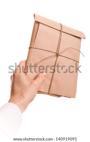 Male hand holds envelope tied with a rope isolated on white background  - stock photo