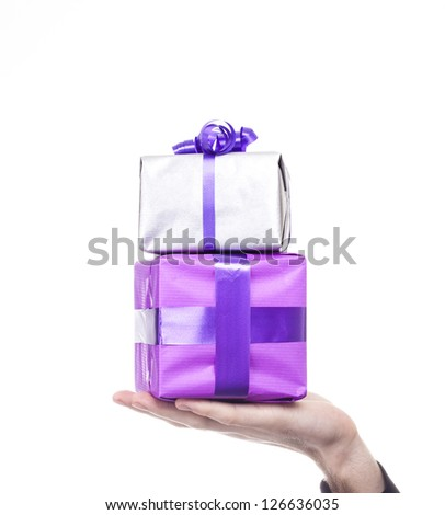 Male hand holds silver and purple gift over a white background. Birthday or Valentine day concept. - stock photo