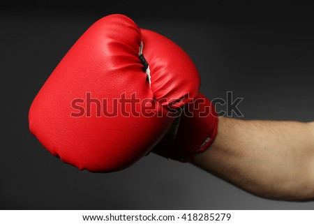 Male hand in boxing glove on grey background