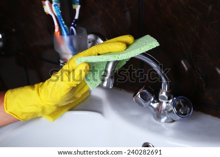Male hand in gloves with sponge cleaning bathroom - stock photo