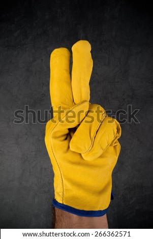 Male Hand in Yellow Leather Construction Engineer or Builder Working protective Gloves Making Two Fingers Gesture. - stock photo