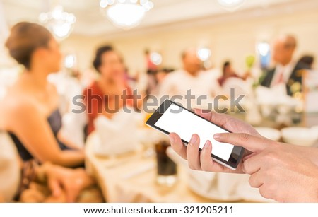 male hand is holding a modern touch screen phone and blur image of wedding party  in large hall for background usage. - stock photo