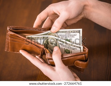 Male hand is taking money from wallet. - stock photo
