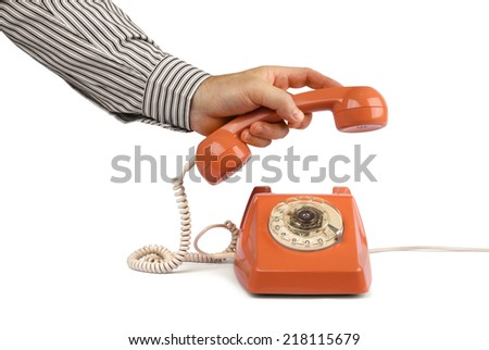 Male hand lifting vintage telephone handset, isolated on white - stock photo