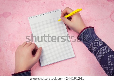 male hand making notes in blank notebook against pink background - stock photo
