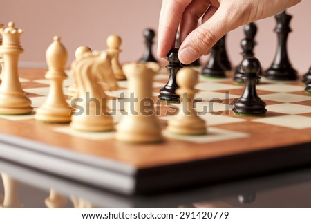 Male hand moving the black pawn in focus on the wooden chessboard in the middle of a chess game - stock photo