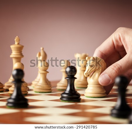 Male hand moving the white chess knight in focus in the middle of a chess game - stock photo