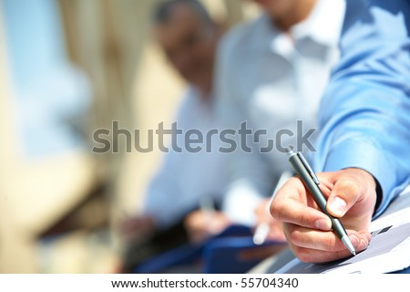Male hand over paper making notes at seminar - stock photo