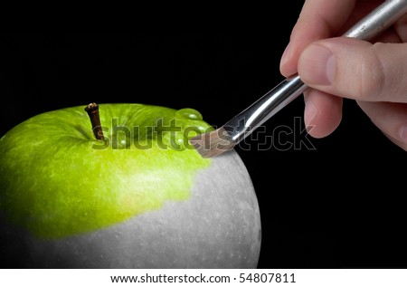 Male hand painting a fresh green wet apple which is partly black and white and partly colored - stock photo