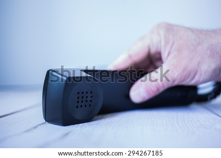 Male hand picking up receiver of a classic land line telephone from a wooden table, selective focus with shallow depth of field. - stock photo