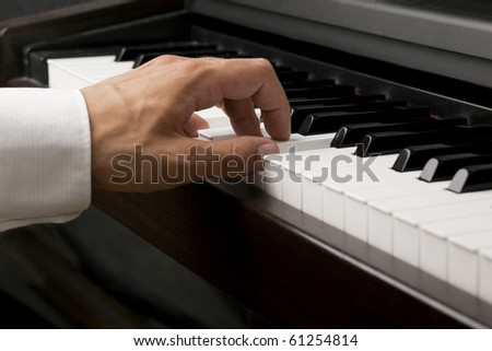 Male hand playing on a piano