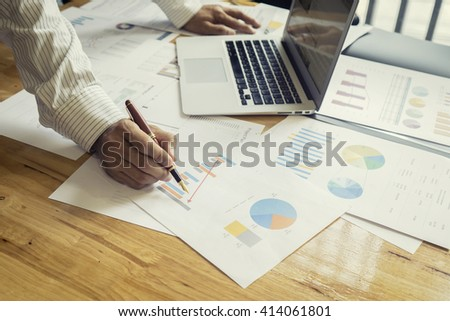 male hand pointing at business chart during discussion at meeting,Business people discussing the charts and graphs showing the results of their successful ,selective focus,Vintage tone,copy space