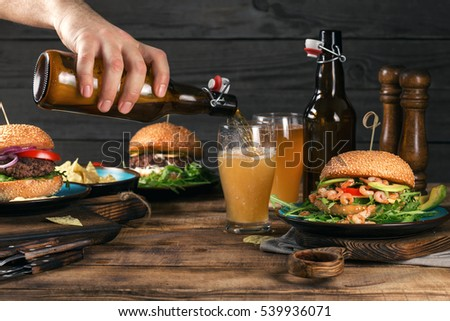 Male hand pours lager beer in glass standing on a wooden table with a variety of burgers