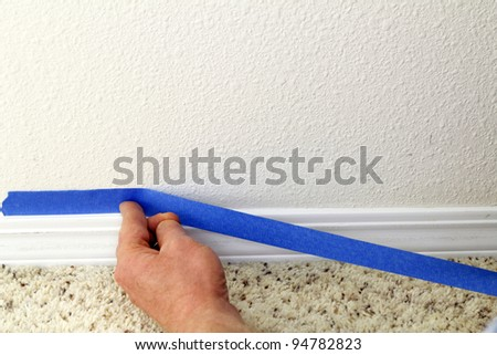 Male hand preparing to paint wall trim by placing blue painter's tape on the wall above it for protection. - stock photo