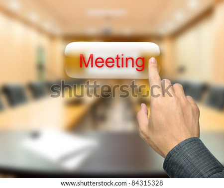 Male hand pressing meeting button on meeting room background - stock photo