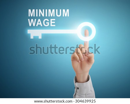 male hand pressing minimum wage key button over blue abstract background - stock photo