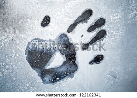 Male hand print on frozen windows glass - stock photo
