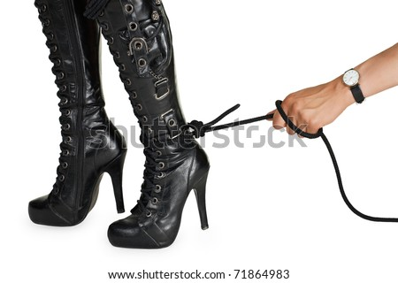Male hand pulling a rope tied to female leg - stock photo