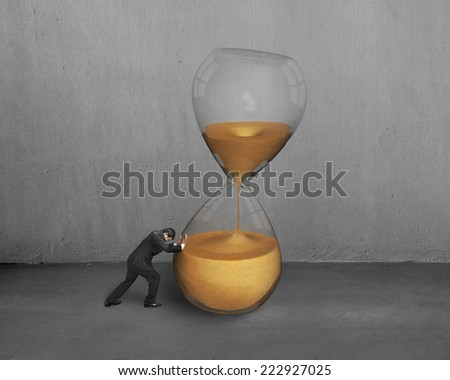 male hand push tilt hour glass with concrete wall - stock photo