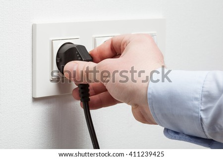 Male hand puts plug in the socket, closeup shot - stock photo