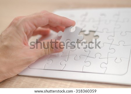 Male hand putting a missing piece and solving blank white jigsaw puzzle placed on top of old wooden oak table, close up, selective focus