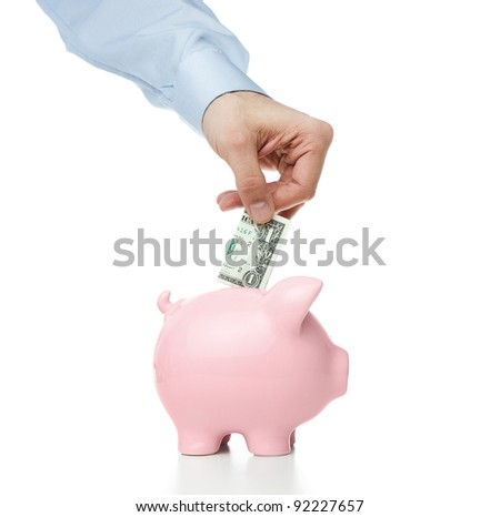Male hand putting dollar bill into a piggy bank - stock photo