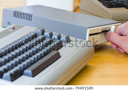 Male hand putting in a disc in a disc drive to an old vintage computer - stock photo
