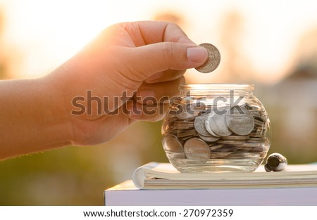 Male hand putting money coins on book with sunlight, Saving for education fund concept