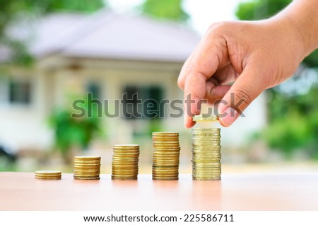 Male hand putting money coins stack like growing graph with home, Saving for buy home concept - stock photo