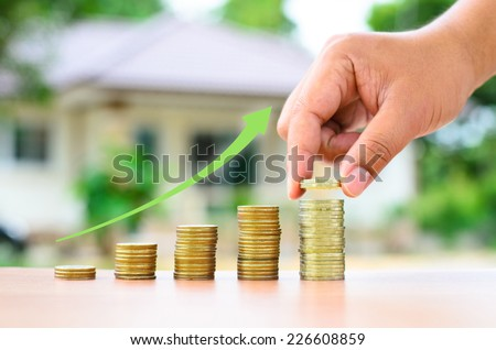 Male hand putting money coins to stack with home and graph, Saving for buy home concept - stock photo
