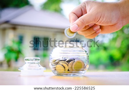 Male hand putting money coins with home, Saving for buy home concept - stock photo