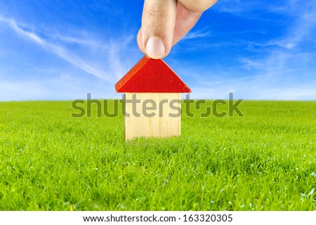 Male hand putting wooden toy house on beautiful green meadow. Concept on planing to build a house in safe and clean environment. - stock photo