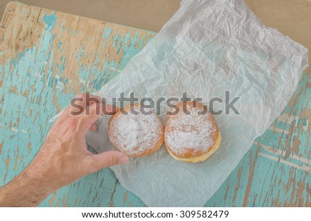 Male hand reaches and taking sweet sugary donut from rustic wooden kitchen table, tasty bakery doughnuts overhead shot, top view - stock photo