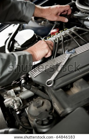 Male hand repairing car engine - stock photo